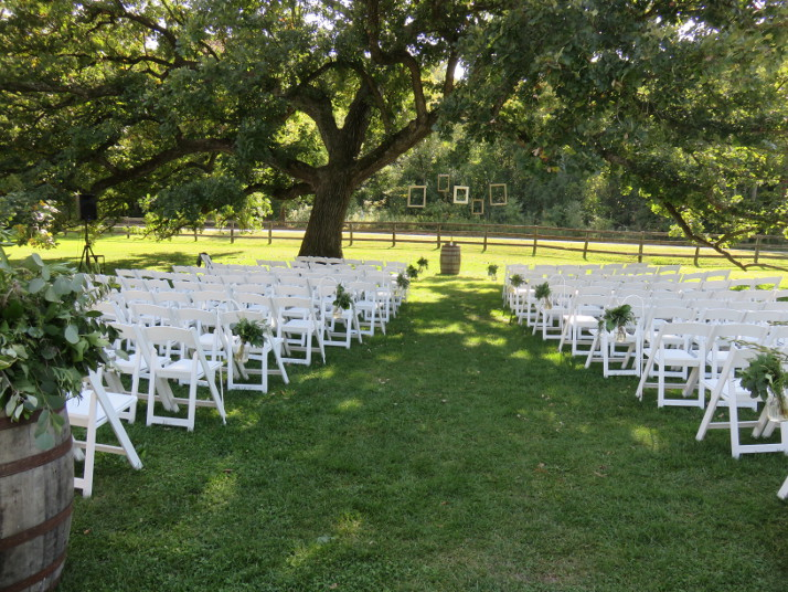 Picture frames and simple greenery decorate outdoor ceremony space